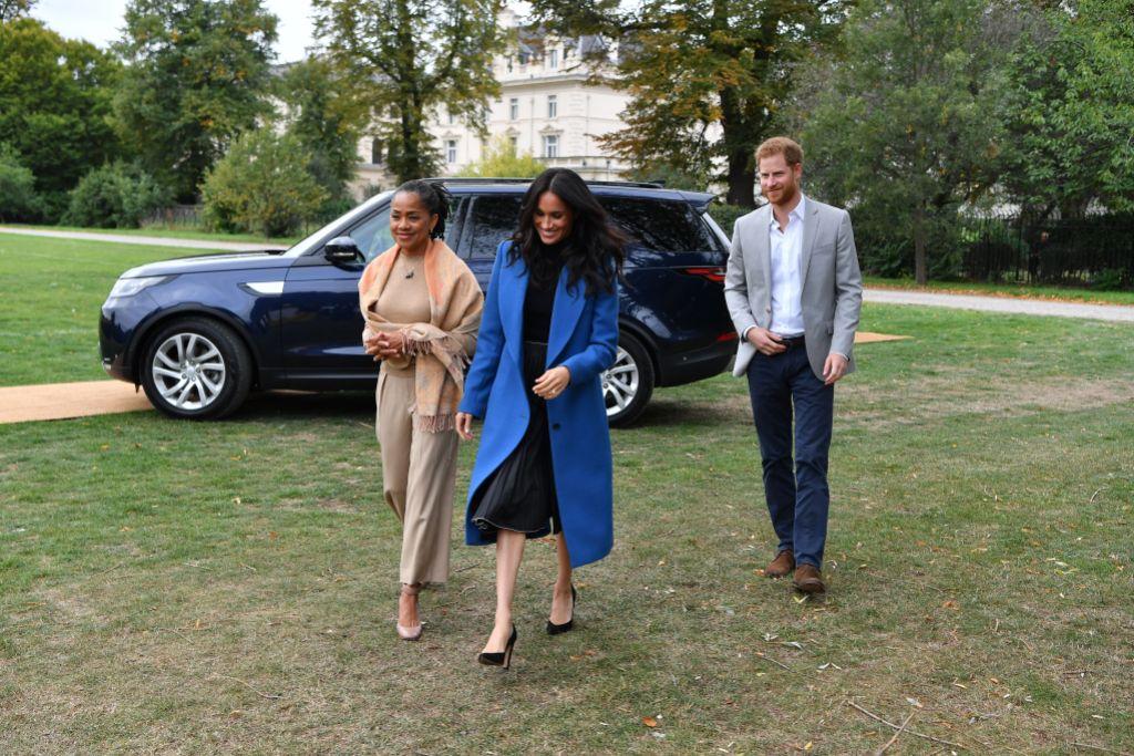 Doria Ragland, Meghan Markle and Prince Harry walking across the grass of Kensington Palace