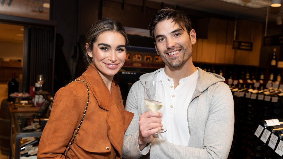 Ashley Iaconetti Wearing a Brown JAcket With Jared Haibon Wearing a Sweatshirt While Holding a Glass of Wine