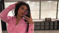 Kylie Jenner taking a selfie in a pink Chanel shirt