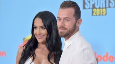Nikki Bella and Artemchigvintsev posing and wearing all white