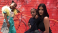 Kim Kardashian posing with Saint West and North West in front of a red wall in Japan