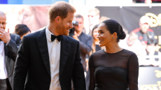 Prince Harry and Meghan Markle smiling at each other on the red carpet of The Lion King