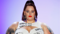 """Tess Holliday walking the catwalk in a white dress with the words """"sample size"""" printed on it"""