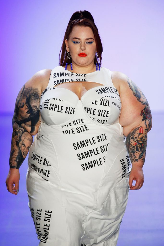 "Tess Holliday walking the catwalk in a white dress with the words ""sample size"" printed on it"