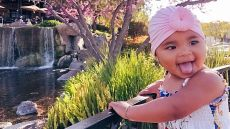 True Thompson sticking her tongue out wearing a pink turban