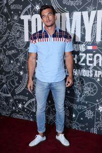 'Bachelorette' alum Tyler Cameron wearing a blue shirt and denim jeans
