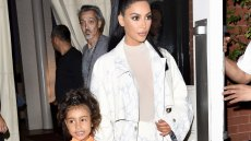 kim kardashian wears off-white top, white jacket and white pants and holds hands with daughter north who is wearing a peach kimono style dress