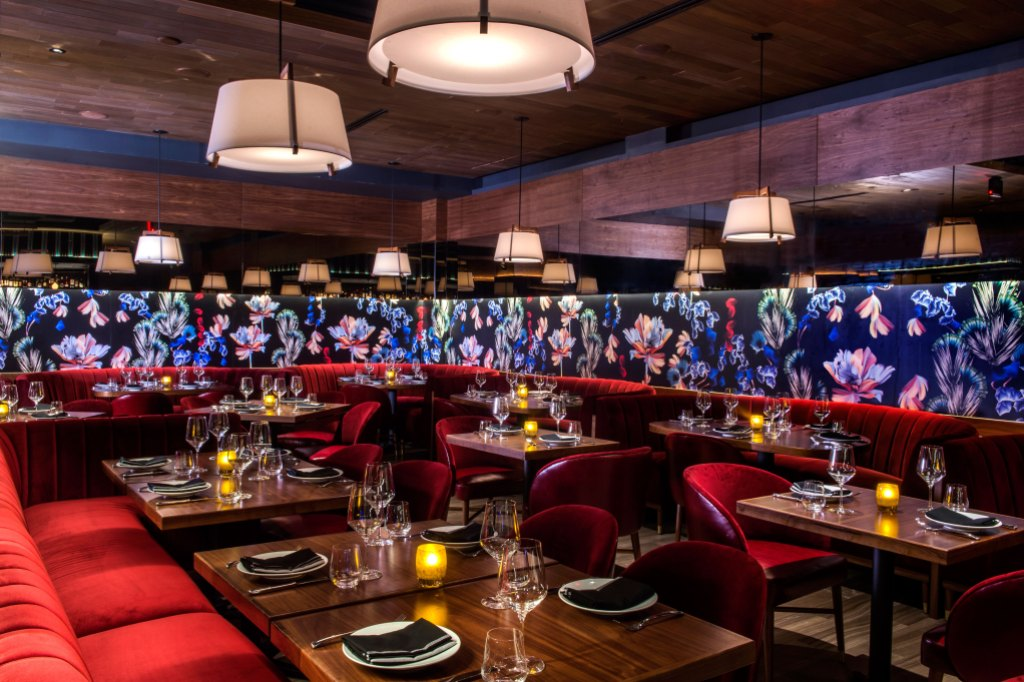 the interior of papi steak features red velvet seats, hardwood table tops and an exotic floral print on the walls