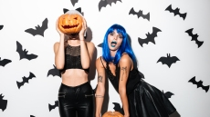 Two Women in Hallowen Costumes Holding Pumpkins