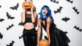 Two Women in Hallowen Costumes Holding Pumpkins