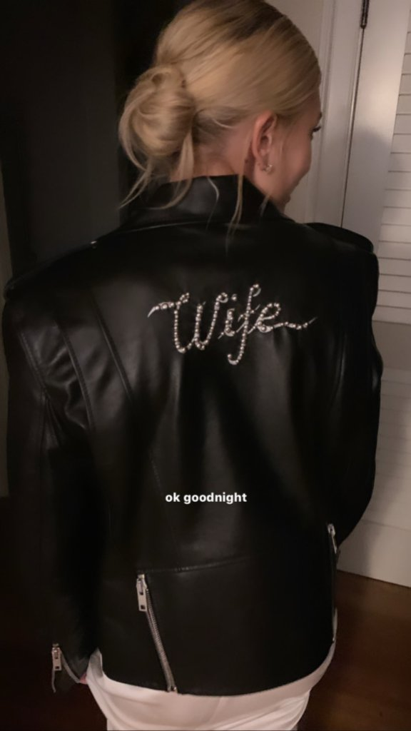 "Hailey Baldwin wearing a leather jacket that says ""wife"" over her wedding dress"