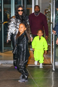North West in Black Coat and Saint West in Lime Green Jumpsuit in NYC