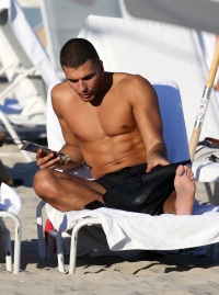 Younes Bendjima Reads Shirtless on the Beach