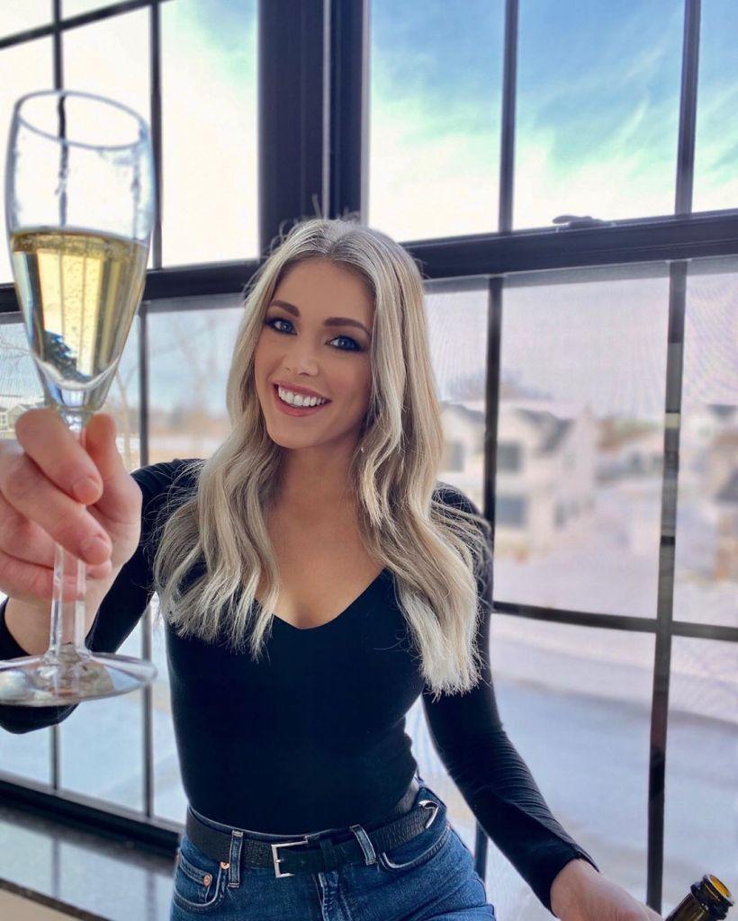 Kelsey Weier Holding a Bottle of Champagne