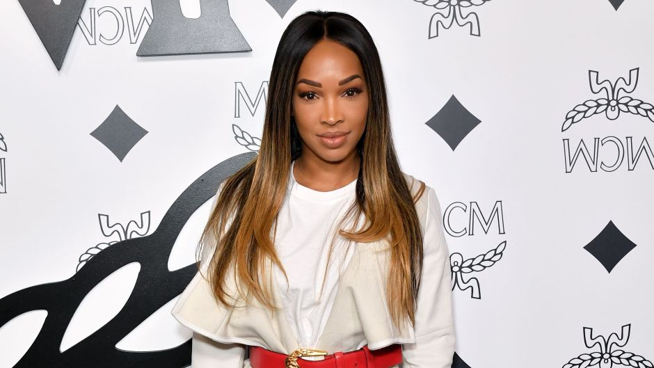Malika Haqq Wears White Dress and Tan Boots While Posing on Red Carpet