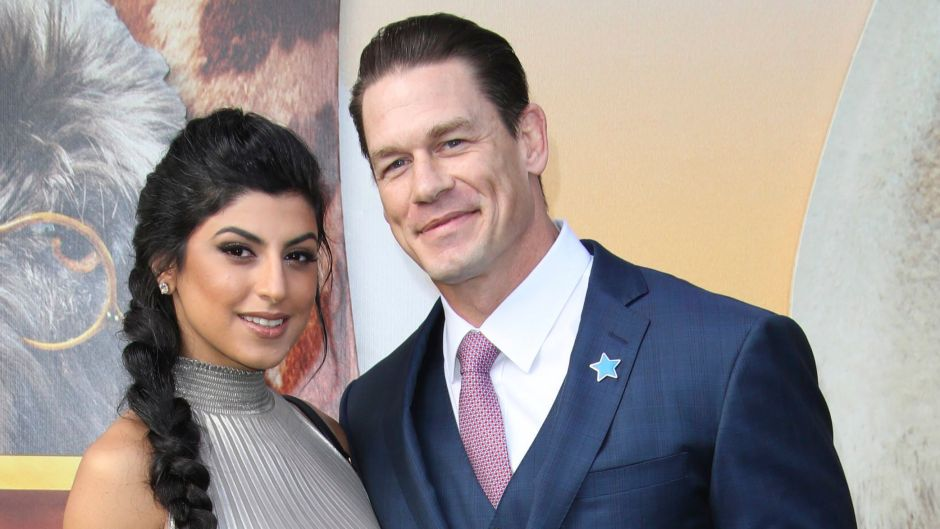 John Cena in Blue Suit and Pink Tie and Girlfriend Shay Shariatzadeh in Shimmery Silver Dress and Long Braid Smile on Red Carpet