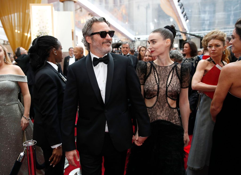 Joaquin Phoenix Wears a Suit With Sunglasses on Red Carpet Holding Hands With Fiance Rooney Mara in Cutout Dress