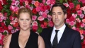 Amy Schumer in Black Gown and Husband Chris Fischer in Blue Suit Stand on Red Carpet Together