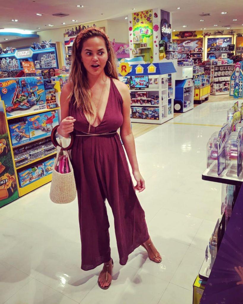Chrissy Teigen Wears Maroon Jumpsuit and Headband in Target