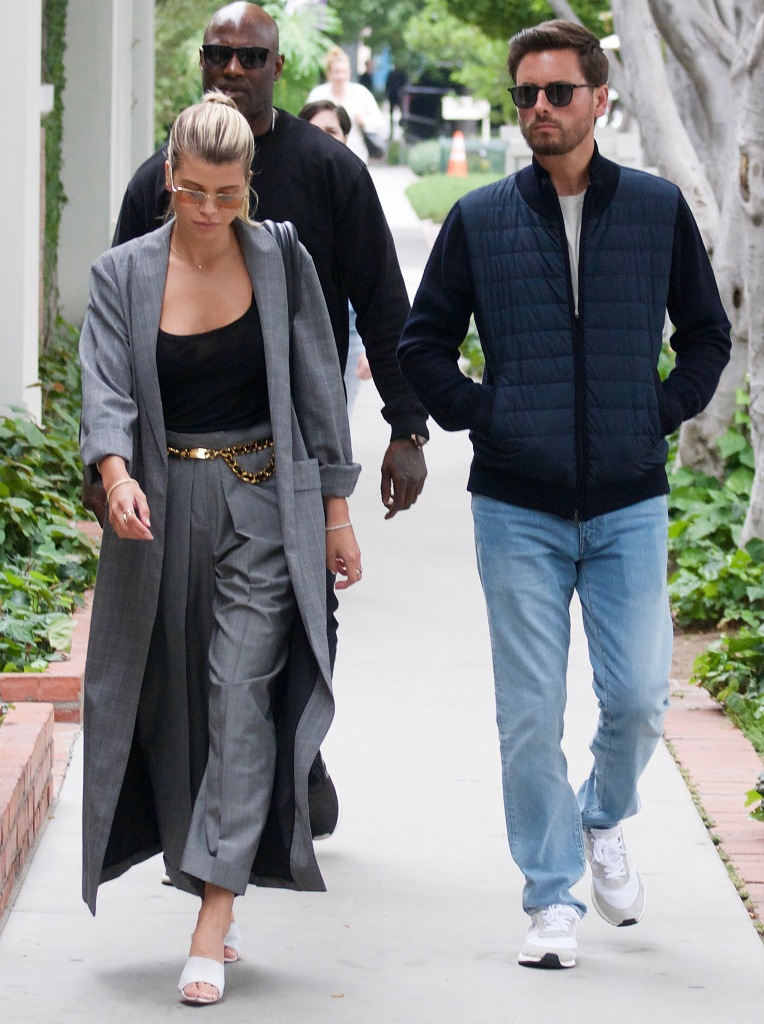 Sofia Richie Walks in Blue Dress Pants Black Tank Top and Long Blue Coat With Sunglasses While Walking WIth Boyfriend Scott Disick in Blue Jeans Blue Jacket and Sunglasses