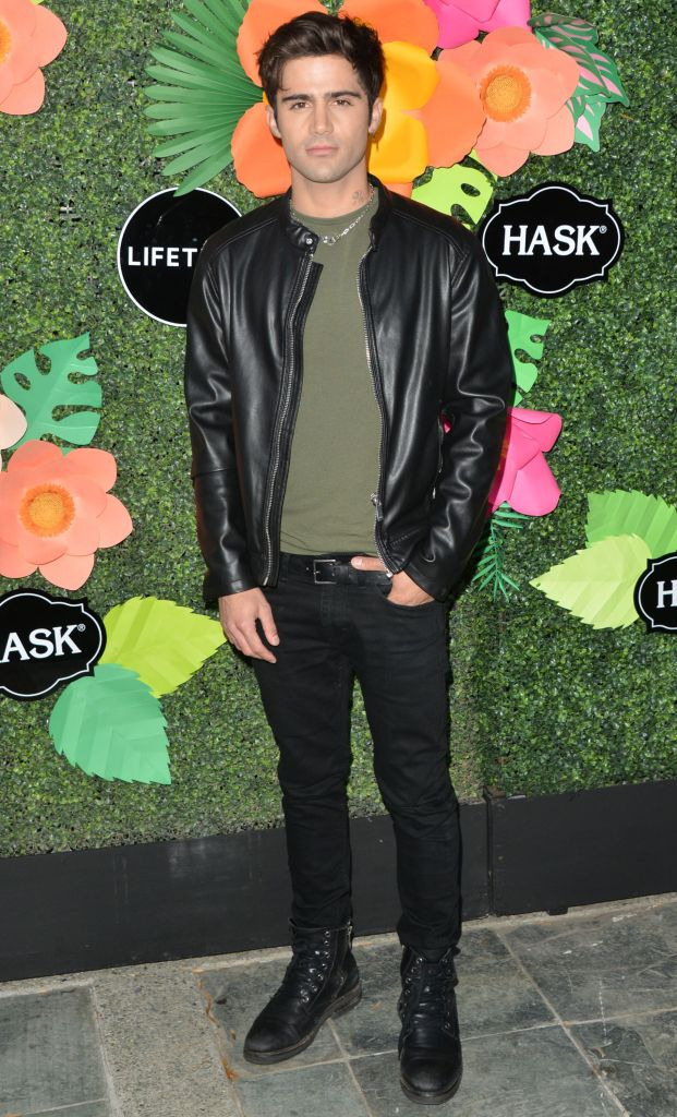 Max Ehrich Stands in Leather Coat and Tshirt