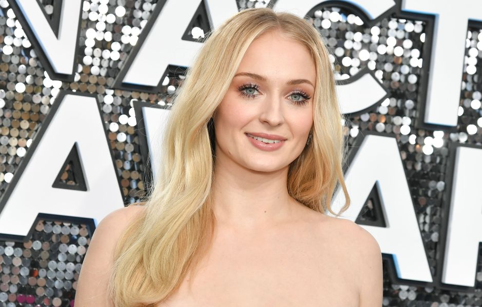 Sophie Turner Smiles in Pink Strapless Dress and Wavy Blonde Hair
