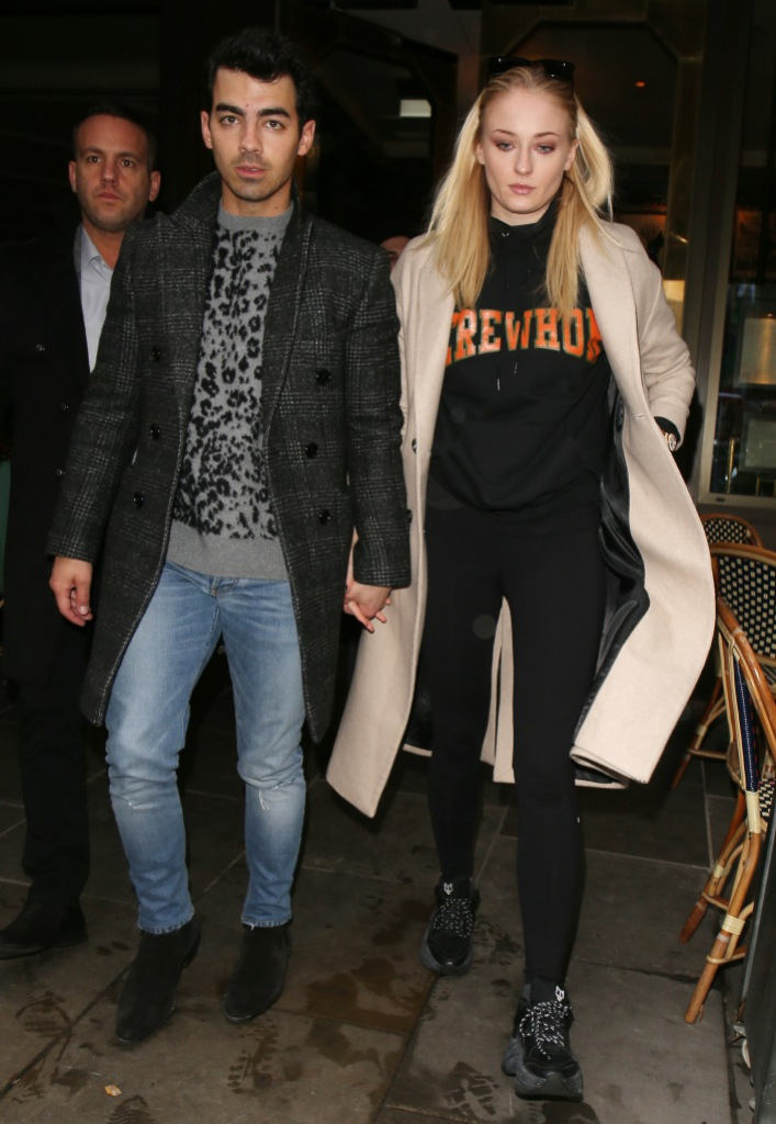 Joe Jonas Wears Jeans a Leopard Print Sweater and Long Coat Holding Hands With Wife Sophie Turner in Black Sweats and Tan Coat