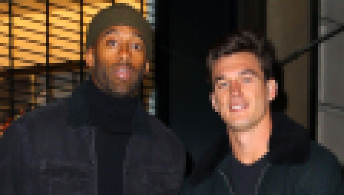 Tyler Cameron Wears Coat With Fur Collar standing Next to Matt James in Beanie and Black Coat