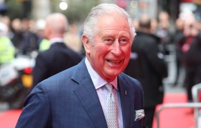Prince Charles Smiles in Blue Suit With Purple Tie