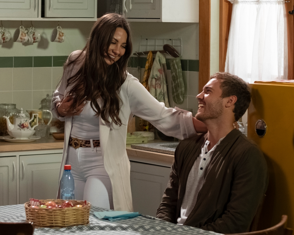 Bachelor Peter Weber Sits and Smiles in a Chair and Looks at Kelley Flanagan Laughing in White Jeans and Sweater with Cheetah Print Belt