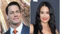 John Cena Smiles in Blue Suit and Orange Tie Nikki Bella Wears Black Crop Top and Red Lipstick