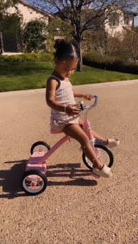 True Thompson Riding a Pink Tricycle