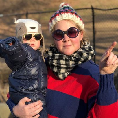 Amy Schumer Smiles Wearing Sunglasses a Hat and Scarf While Holding Son Gene in a Parka Hat and Sunglasses