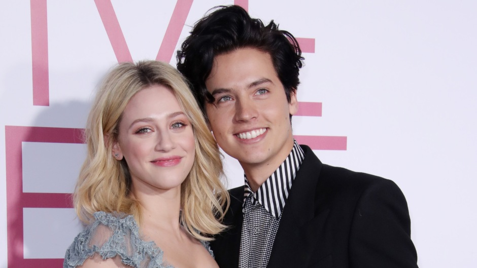 Cole Sprouse Smiles in Black Blazer and Striped Shirt With Arm Around Girlfriend Lili Reinhart in Frilly Dress