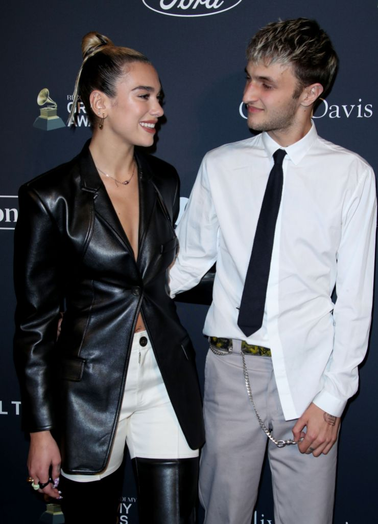 Dua Lipa Wears Leather Coat and White Pants and Laughs With Boyfriend Anwar Hadid in White Untucked Button Down Shirt and Grey Pants