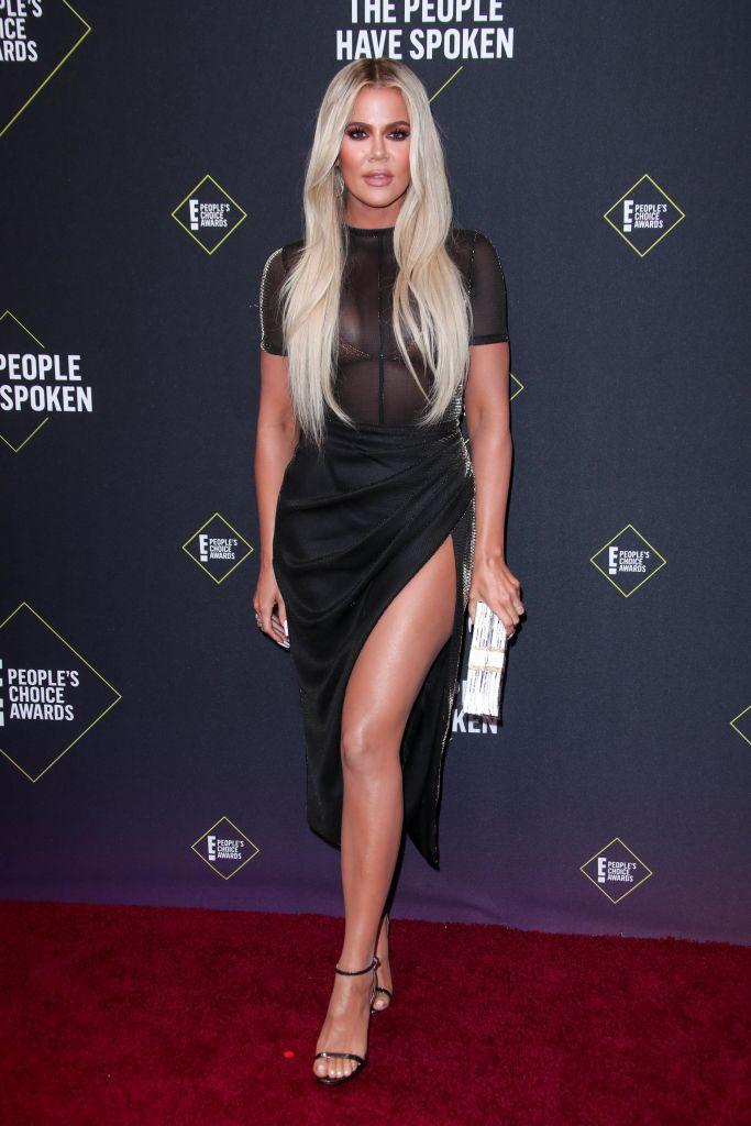 Khlow Kardashian Wears Black Sheer Top and High Slit Skirt With Long Blonde Hair