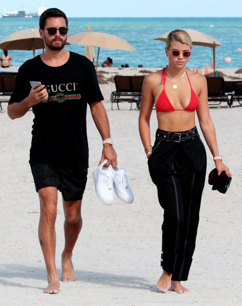 Scott Disick Wears a Black Tshirt and Shorts on Beach With Sofia Richie in Red Bikini Top and Black Pants